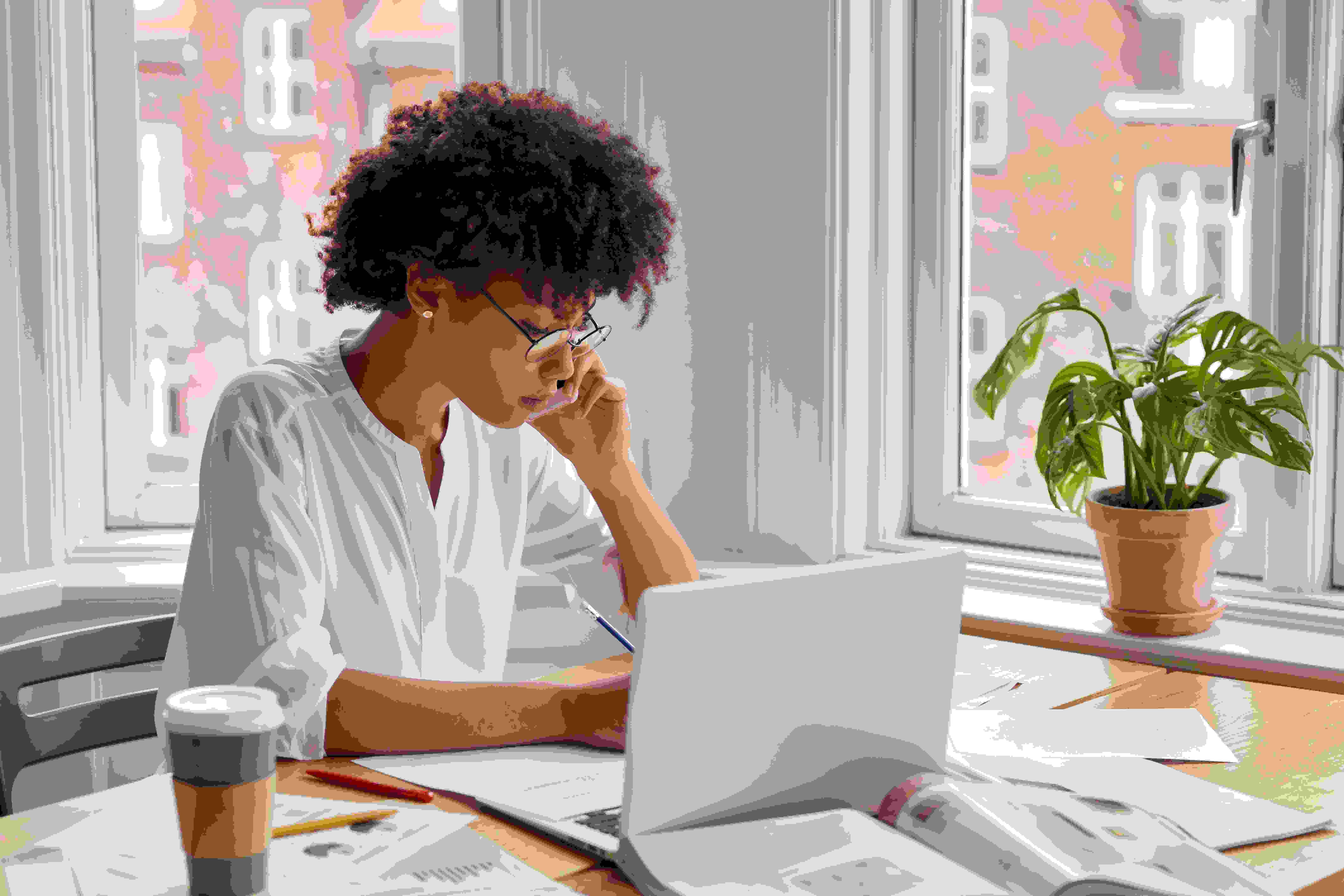 Mulher sentada de frente a um notebook branco, falando ao telefone e fazendo anotações sobre contrato social MEI