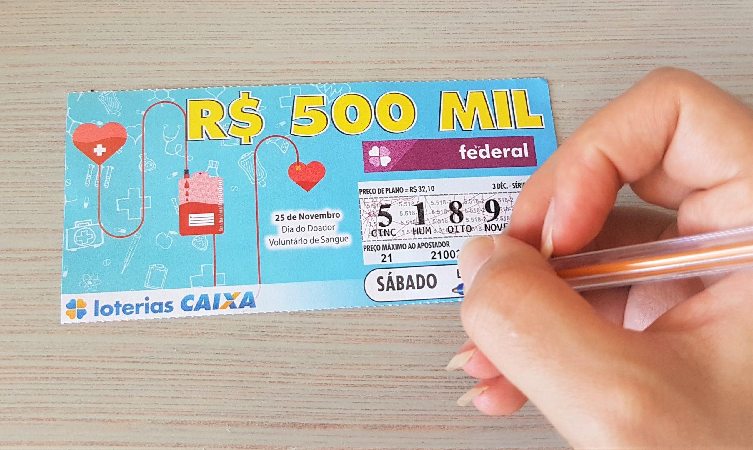 A imagem mostra uma mão segurando uma caneta e um bilhete da loteria Federal 5521