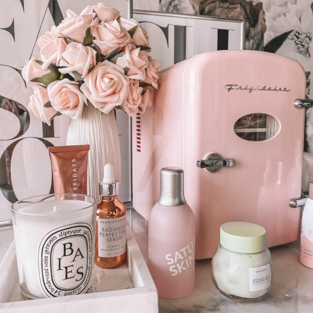 Geladeira rosa em quarto com produtos de skincare