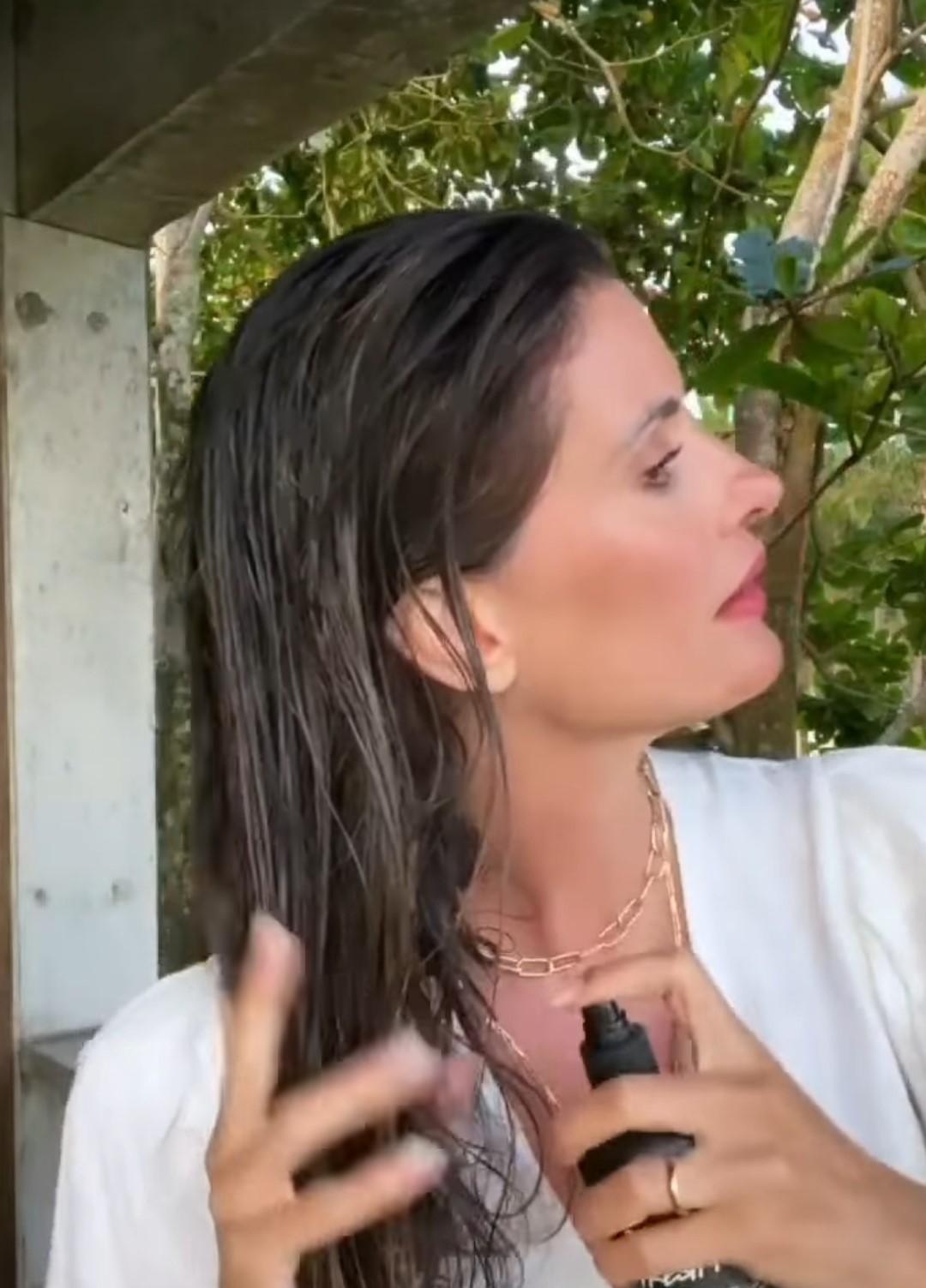 Imagem mostra Isabella Fiorentino aplicando spray nos cabelos