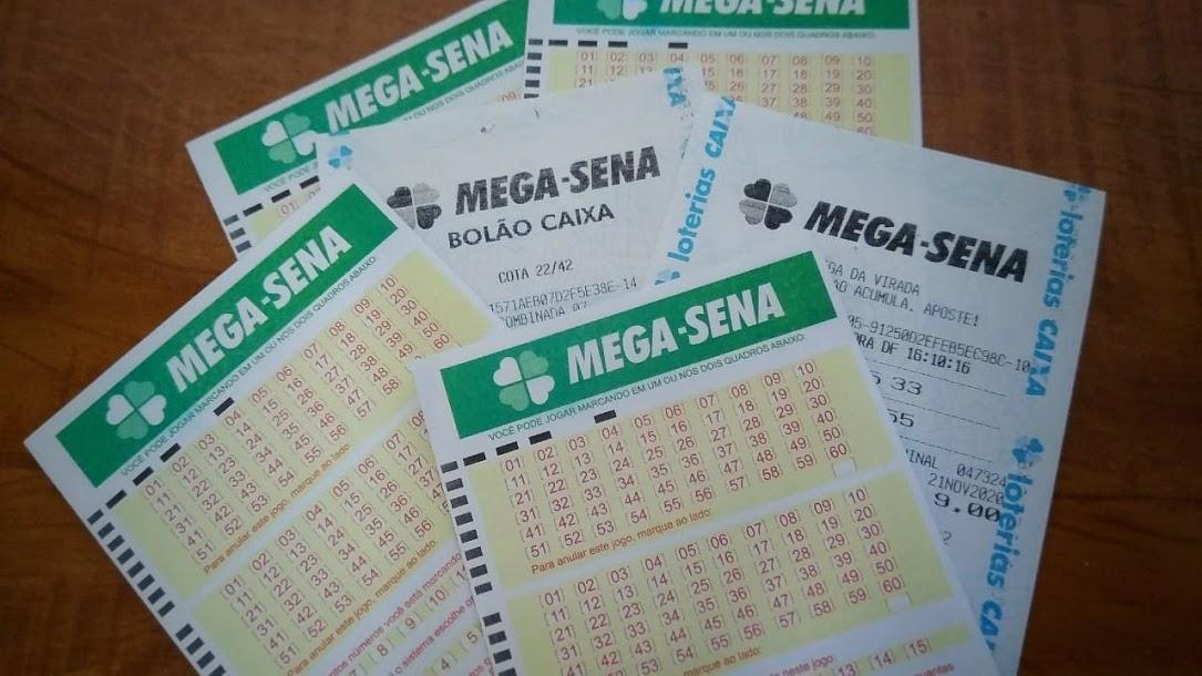 A imagem mostra diversos volantes e apostas da Mega Sena espalhados