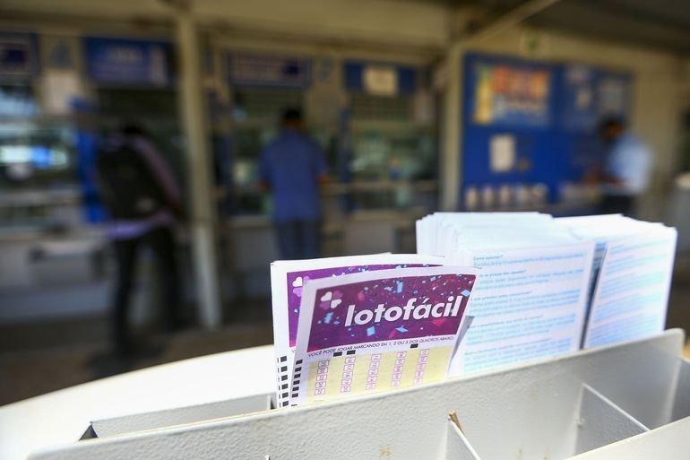 resultados das Loterias Caixa - no primeiro plano, um bilhete da lotofácil e ao fundo uma lotérica descocada, resultado da lotofácil