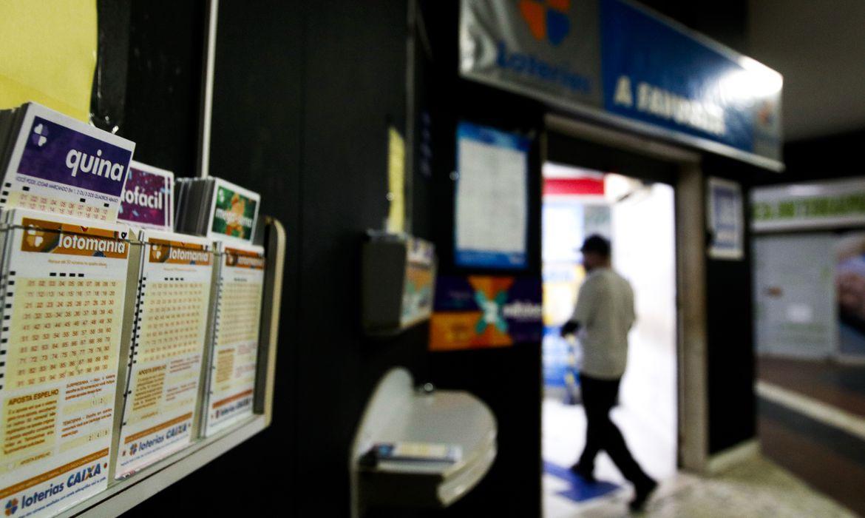 A imagem mostra ao lado esquerdo alguns suportes de parede com volantes das loterias Quina, Lotomania e Mega-Sena. Ao lado direito a está a fachada de uma lotérica - prêmio nas Loterias Caixa