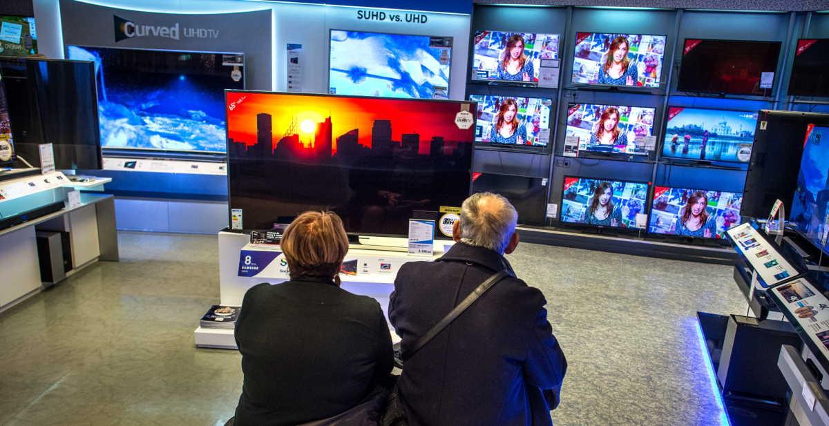Casal sentado na loja vendo TV promoção no Black Friday