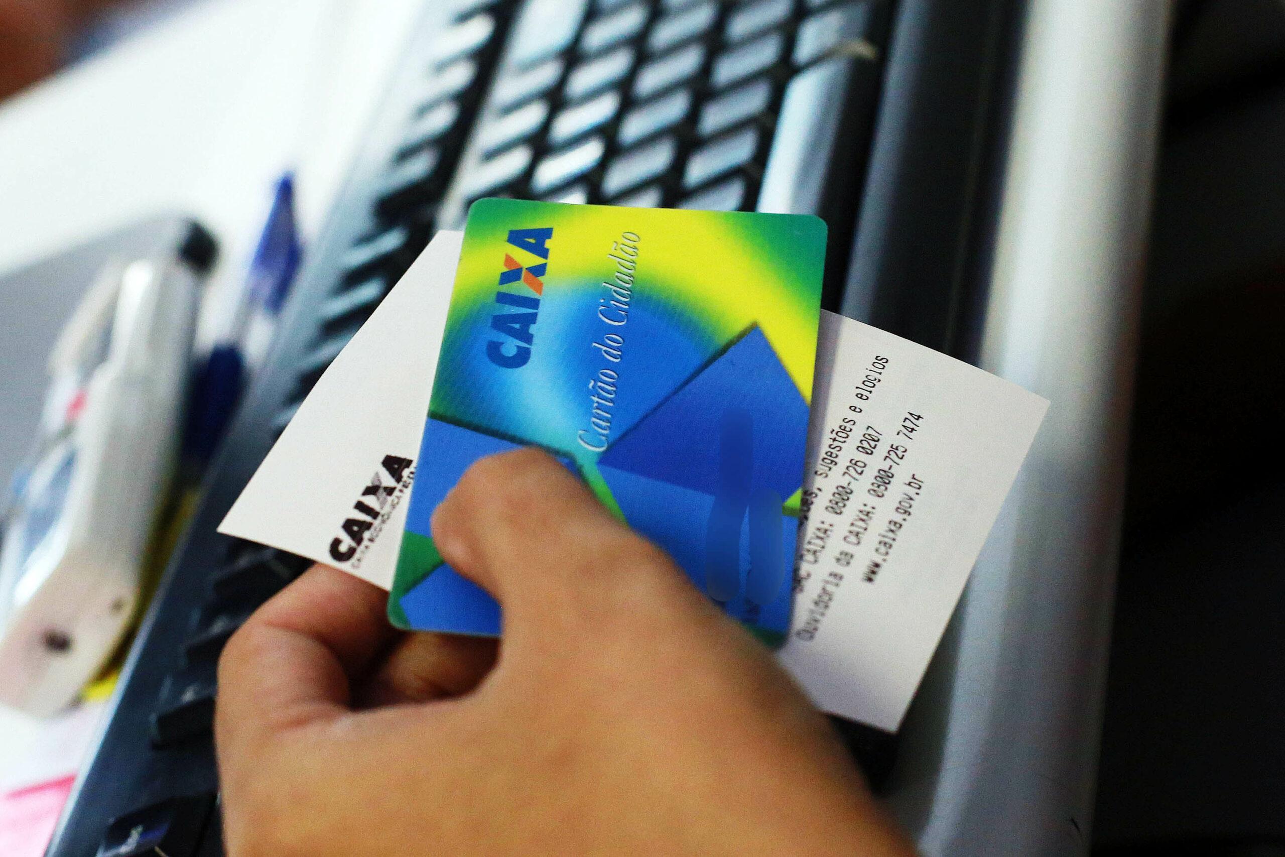 Mãos segurando o cartão cidadão para consulta do PIS/PASEP de 2021.