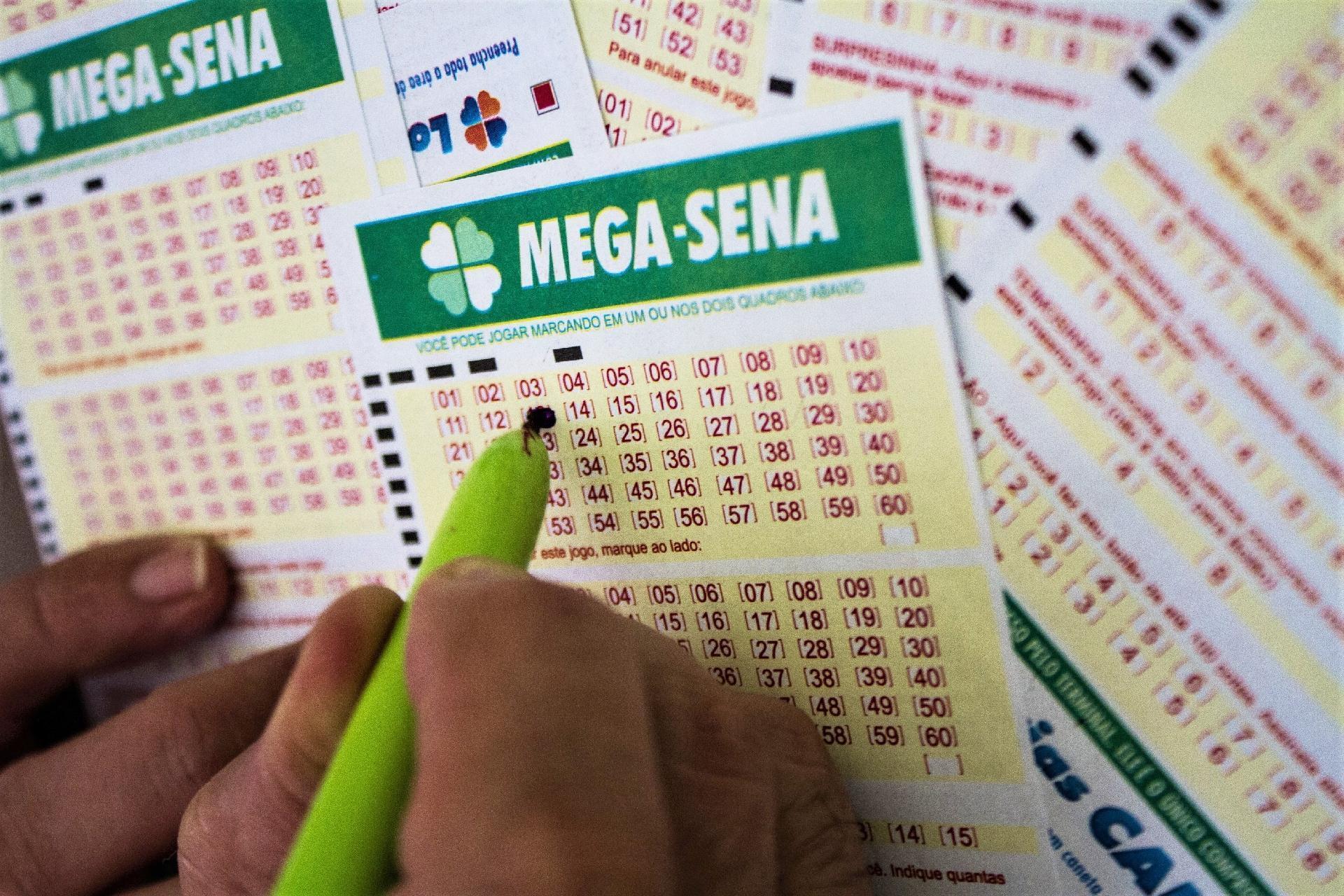 Mega - Sena 2318 - a imagem mostra uma mão segurando uma caneta e marcando números em um volante da Mega - Sena