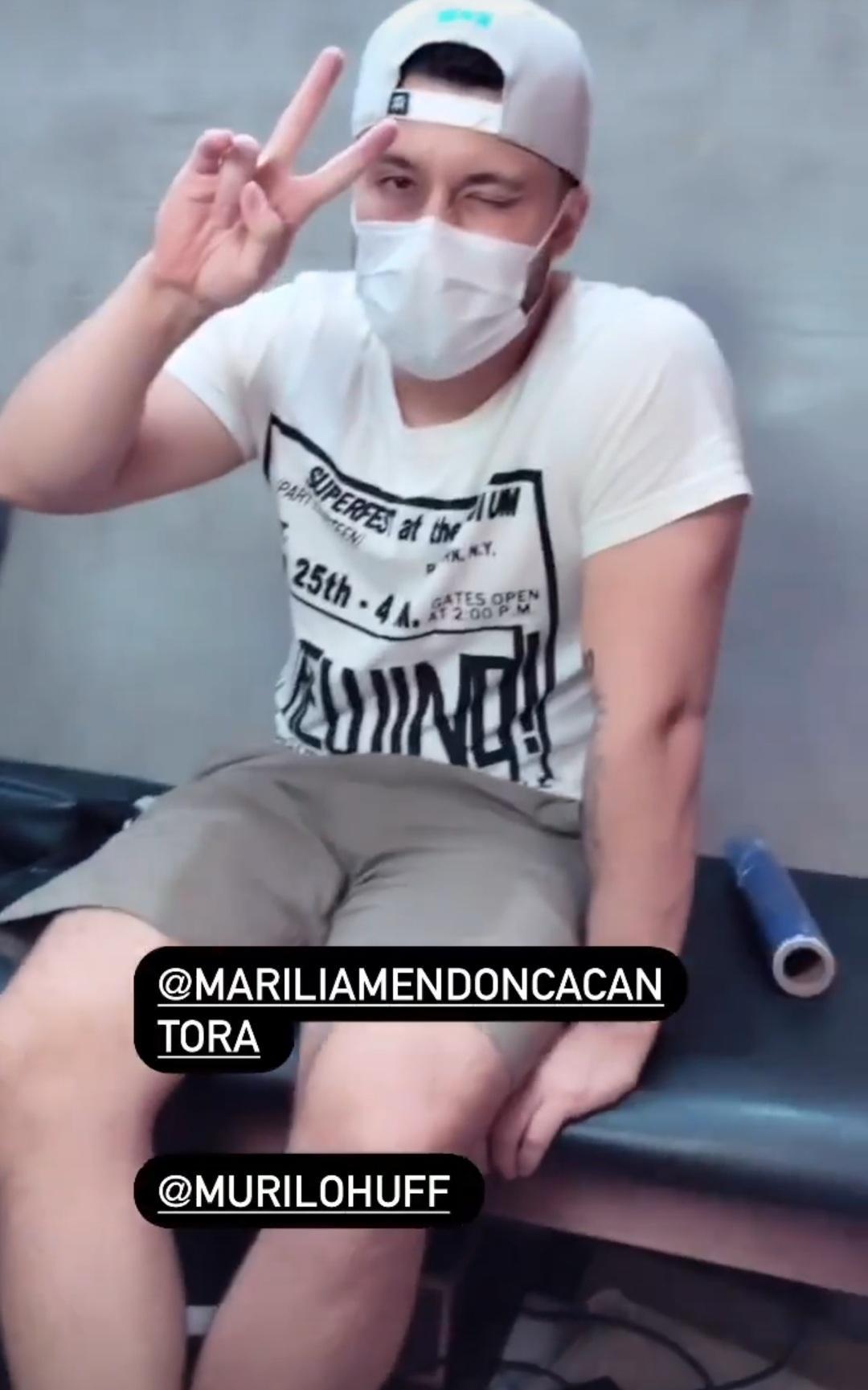 Imagem mostra Murilo Huff de máscara acompanhando Marilia Mendonça, que foi fazer tatuagem