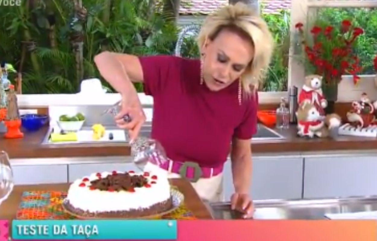 Imagem mostra Ana Maria Braga cortando bolo com a taça