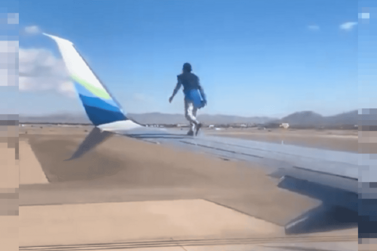 Homem sobe em asa de avião