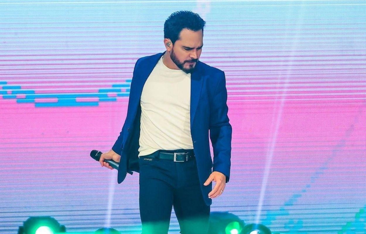Imagem mostra Luciano Camargo com microfone na mão como cantor gospel