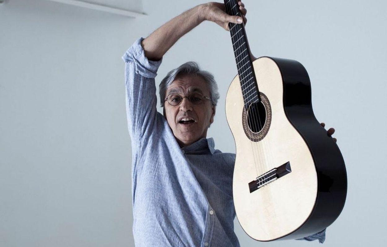 Imagem mostra Caetano Veloso segurando um violão