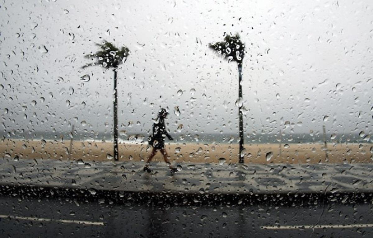Previsão do tempo no litoral: homem anda na chuva na orla da praia