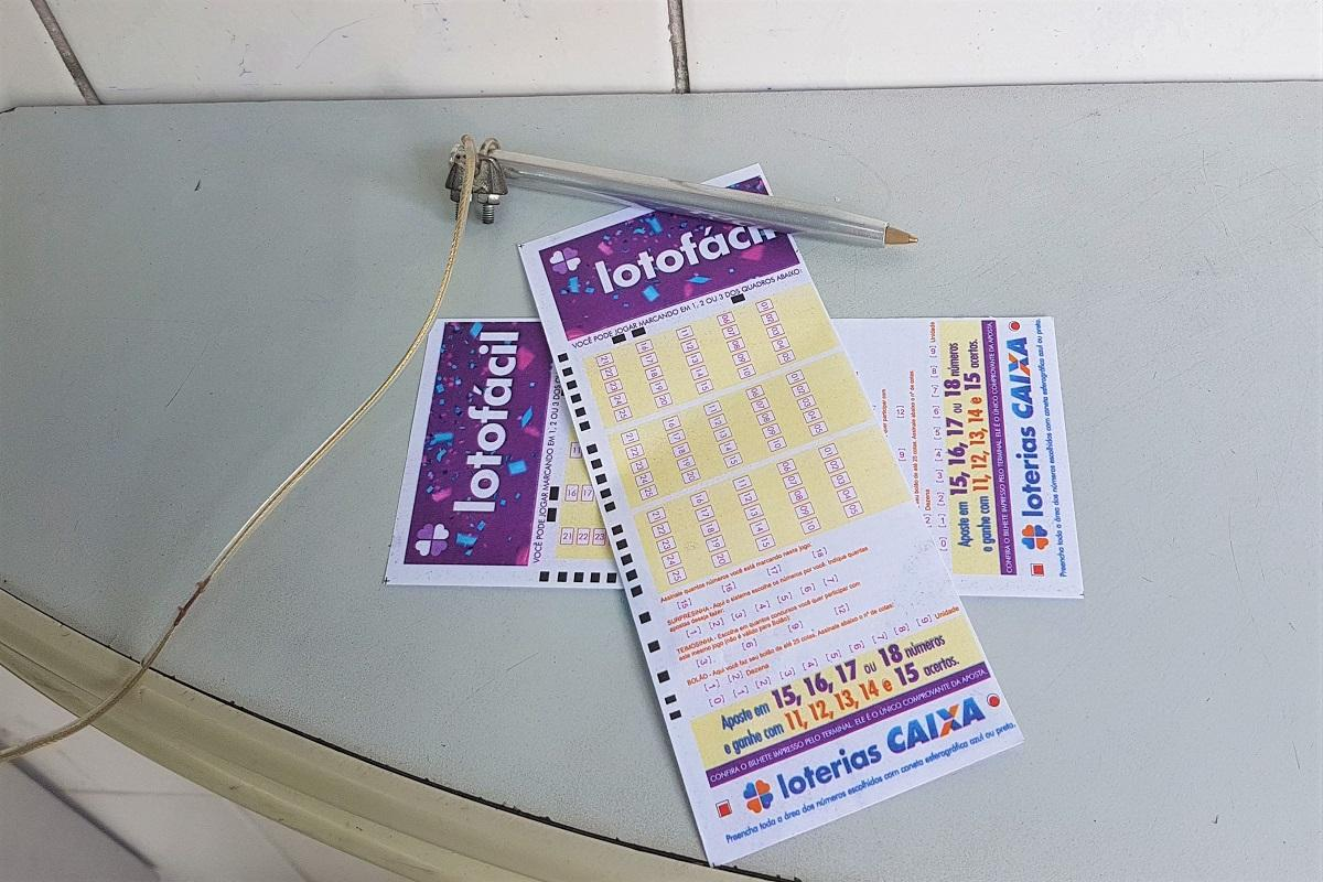 resultado da lotofácil- Uma caneta em cima de dois volantes da Lotofácil