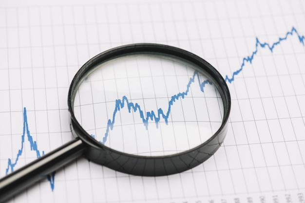 Gráfico de ações e lupa.