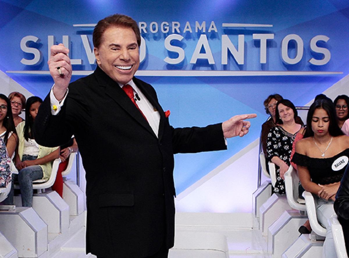 A imagem mostra Silvio Santos apresentando seu programa