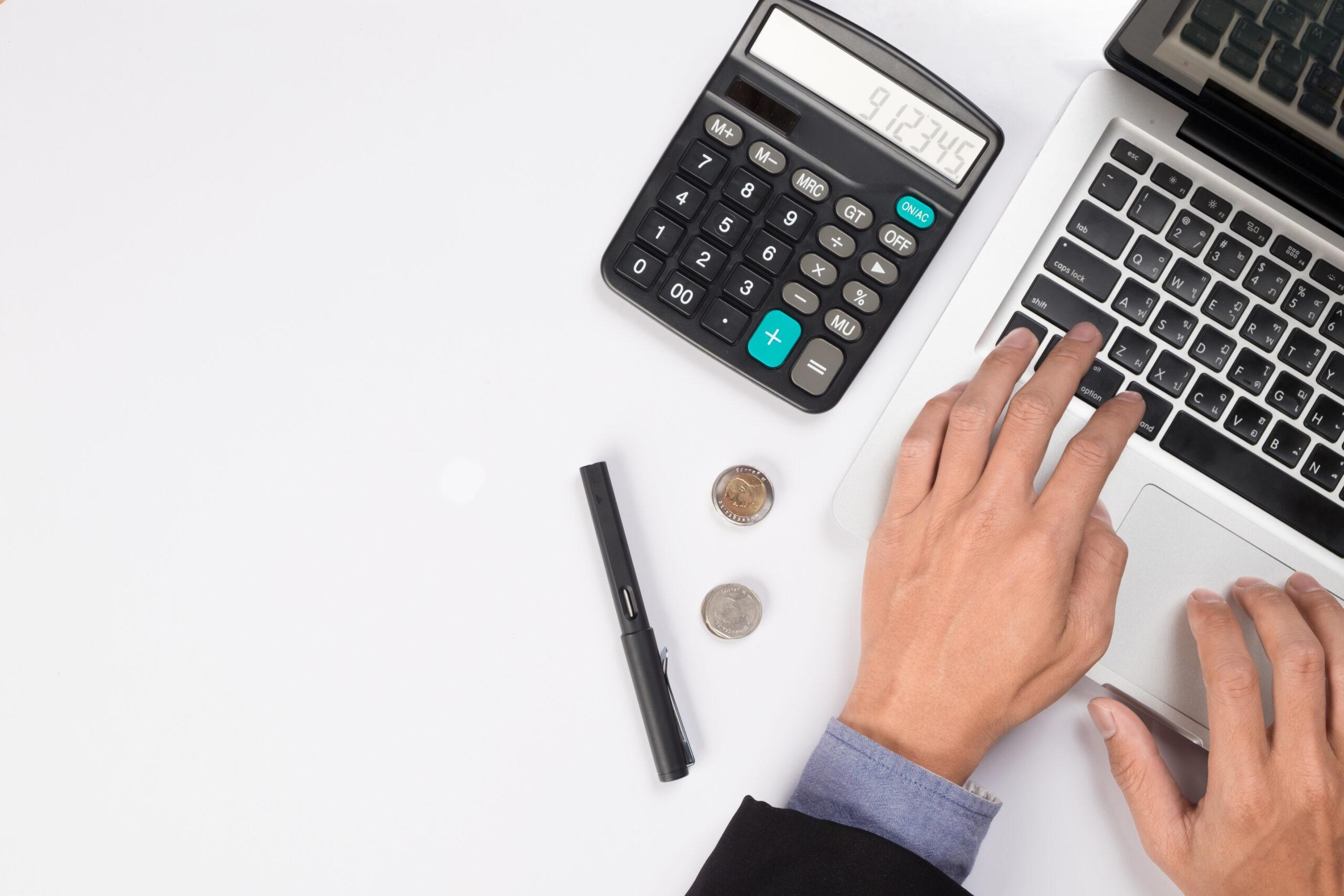 Pessoa usando notebook com calculadora ao lado
