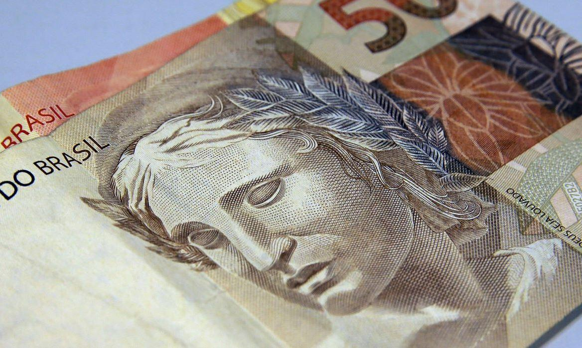 Foto aproximada mostra nota de 50 reais.
