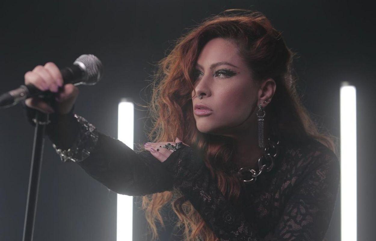 Imagem mostra cantora Pitty com microfone na mão