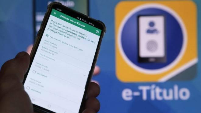 Imagem tem aparelho celular aberto no aplicativo e-Título em matéria sobre como justificar o voto