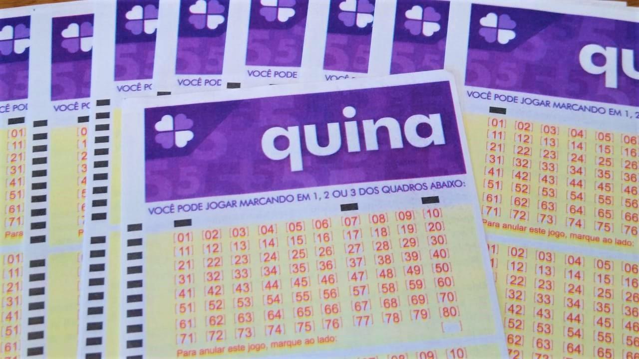 resultado da quina - a imagem contém diversos volantes de aposta da quina em branco sob uma mesa