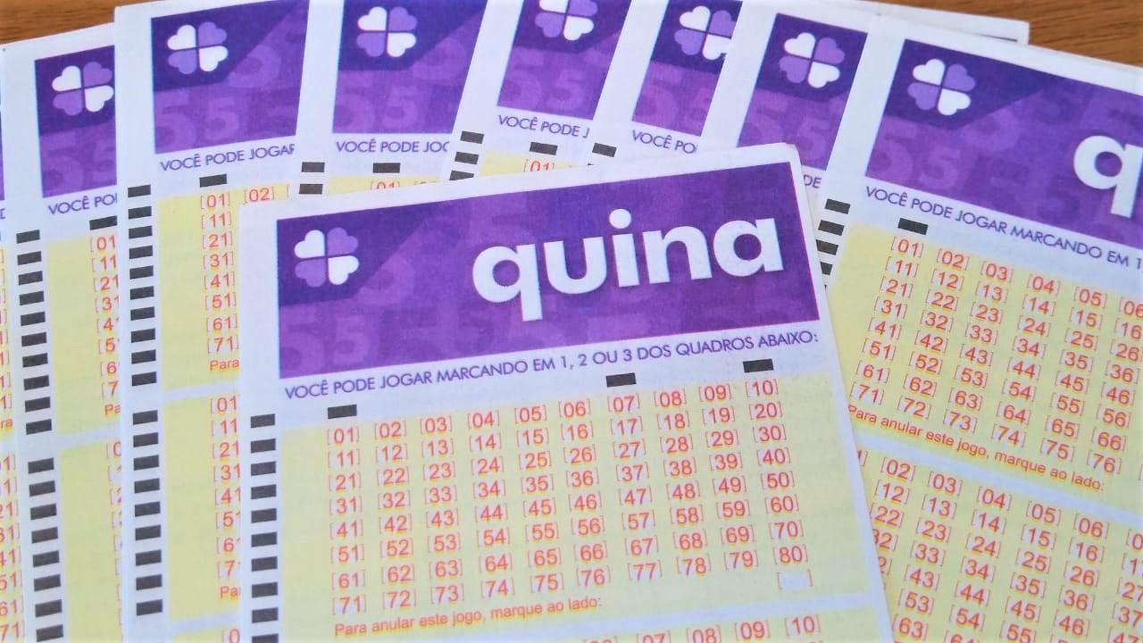resultado da quina - bilhetes da quina em branco espalhados sob uma mesa em formato de leque com um bilhete em destaque por cima dos demais