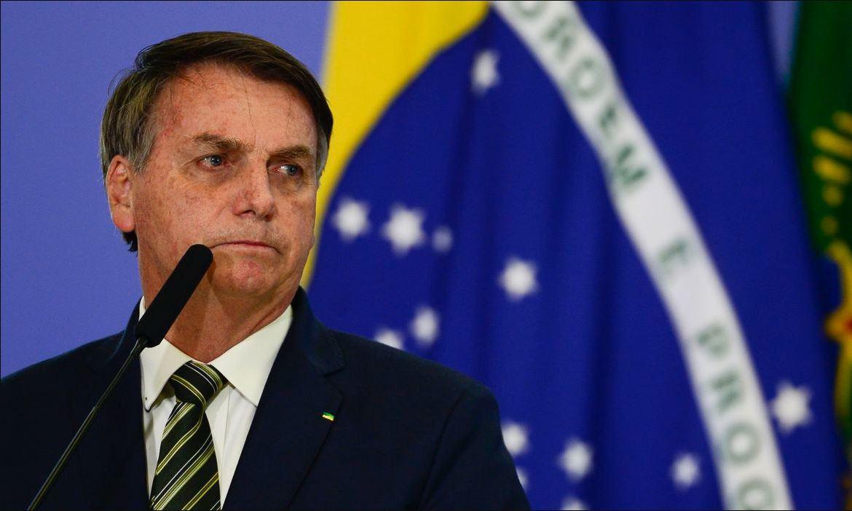 Foto mostra presidente Jair Bolsonaro alinhado a esquerda do enquadramento, vestido de terno, diante de um microfone e com olhar direcionado a direita (sua esquerda). Bandeira do Brasil se encontra ao fundo.