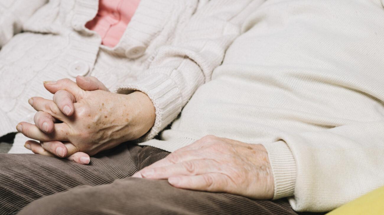 Foto aproximada mostra casal de idosos sentados e de mãos dadas.