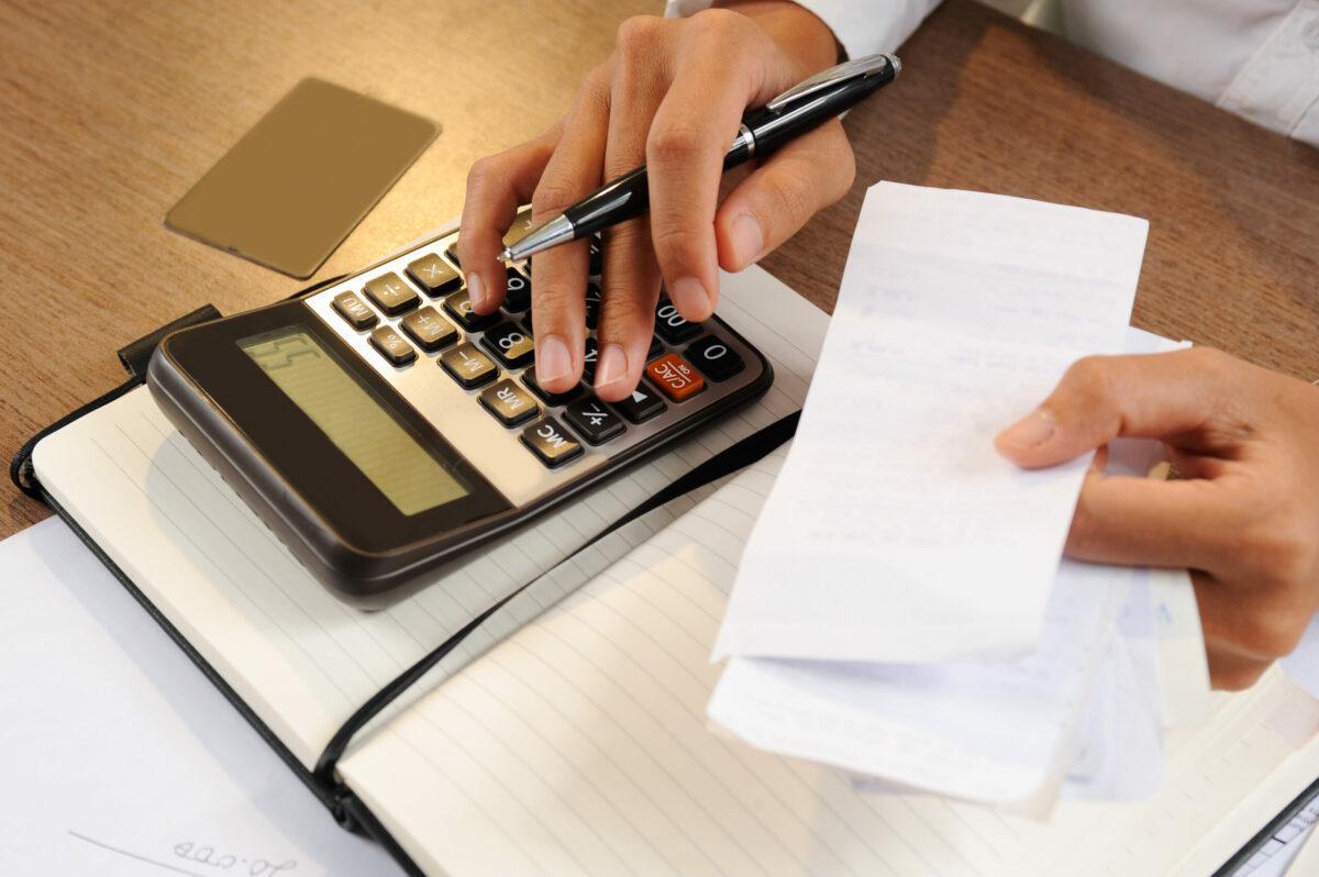 Foto aproximada mostra mãos segurando recibos e contas com a mão esquerda enquanto realiza contas em uma calculadora sobre a mesa de madeira.