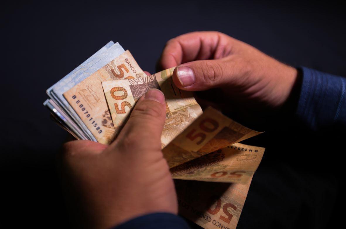Foto mostra mãos segurando diversas notas de 50 e 100 reais.
