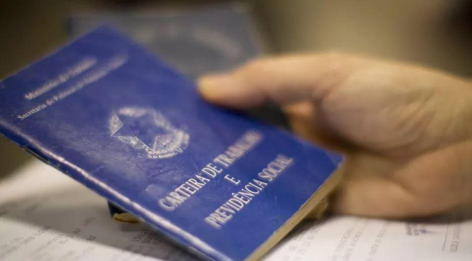 Foto aproximada mostra mãos segurando Carteira de Trabalho.