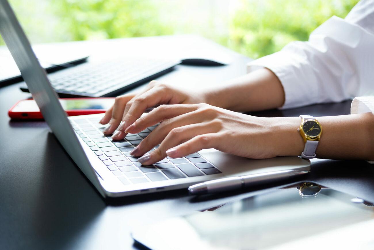 Foto mostra mãos de mulher branca digitando em teclado de notebook sobre a mesa.