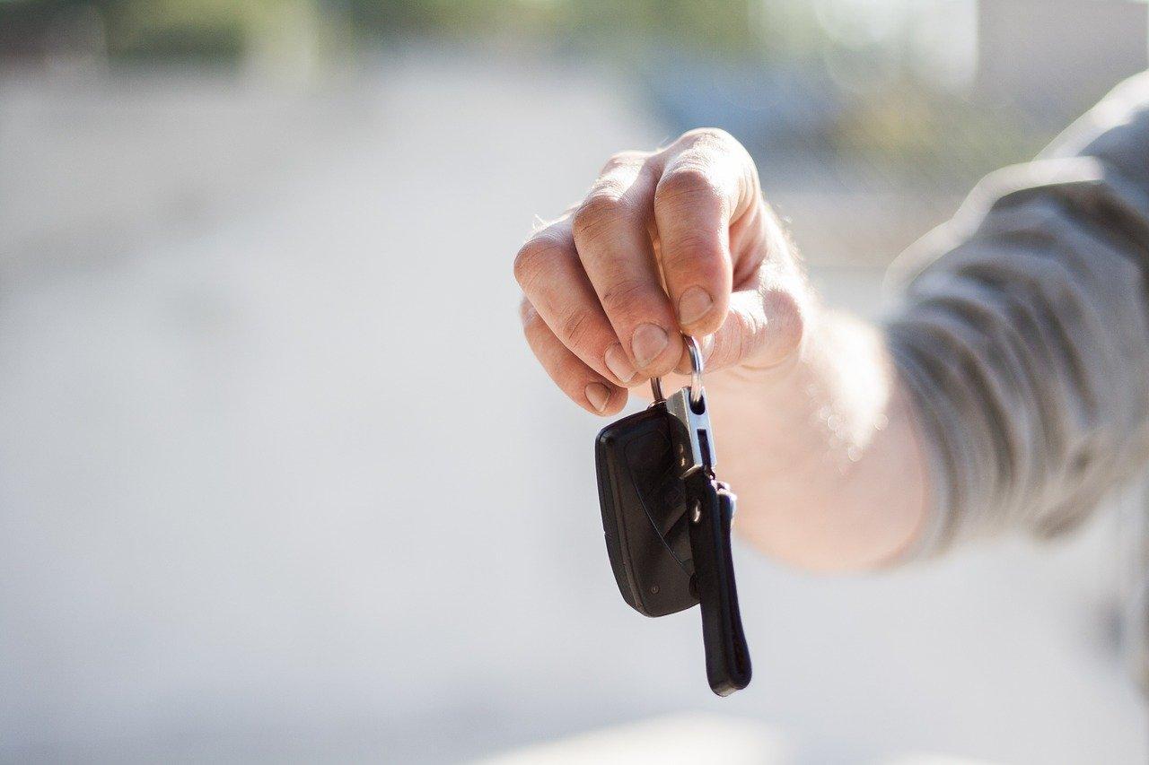Foto aproximada mostra mãos segurando chave de carro.
