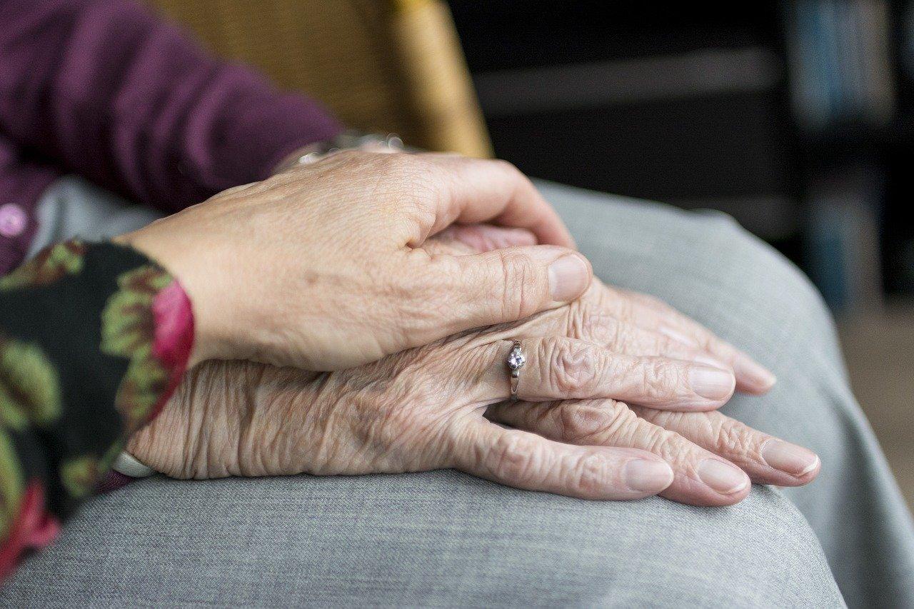 Foto aproximada mostra pessoa idosa com mãos unidas sobre as pernas e mão de pessoa ao lado repousada em cima.