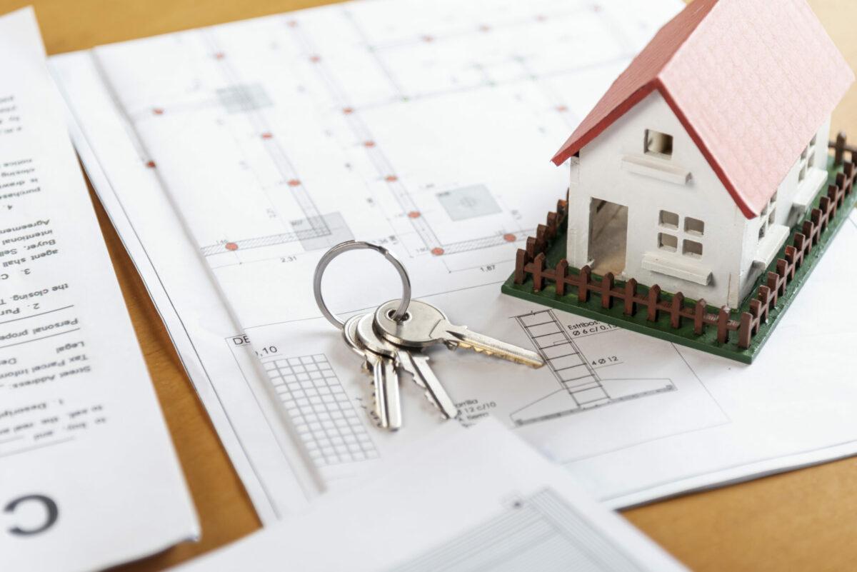 Foto mostra miniatura de casa ao lado de chaves, apoiadas em cima de folha que contém projeto arquitetônico de casa.