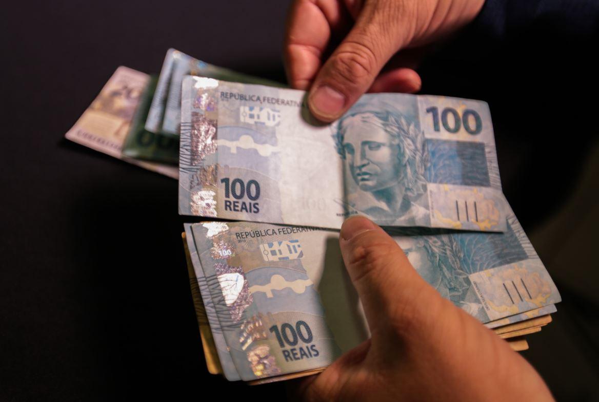 Foto mostra homem contando notas de 100 reais.