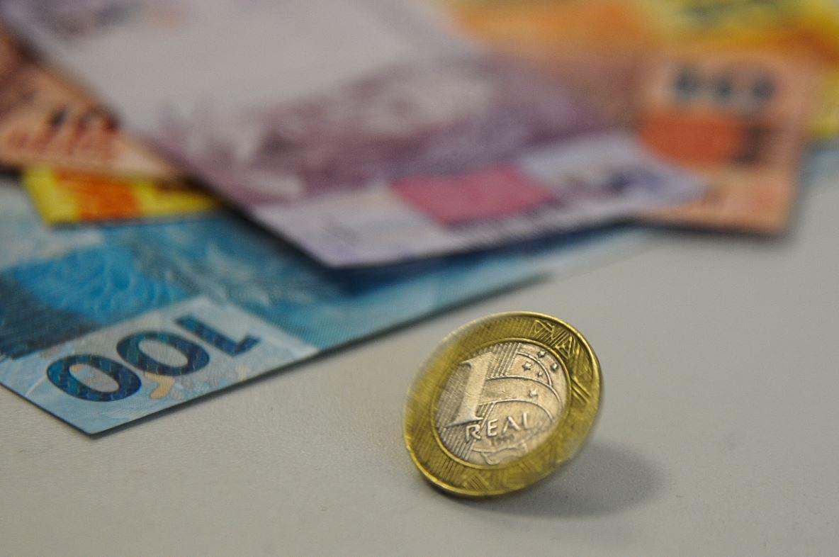 Foto mostra moeda de 1 real ao centro e notas de 100, 10 e 5 reais ao fundo.