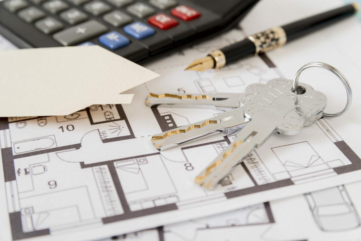 Foto mostra chaves de imóvel em cima de folhas com projetos arquitetônicos e ao lado de uma calculadora.