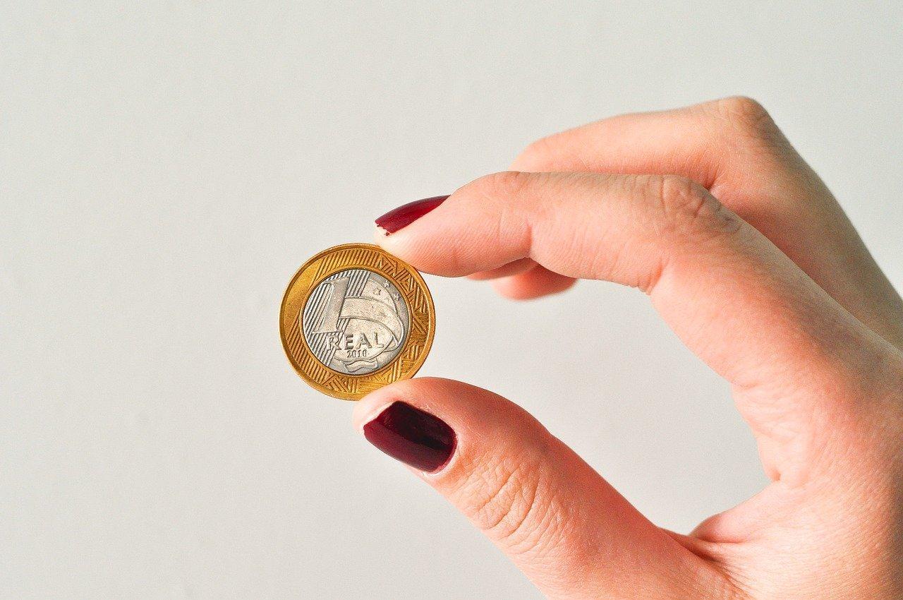 Foto mostra mãos femininas segurando moeda de 1 real.