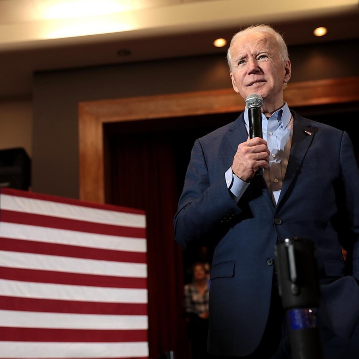 Imagem do novo presidente dos EUA, Joe Biden. Na foto, ele aparece discursando perto de uma bandeira do país.