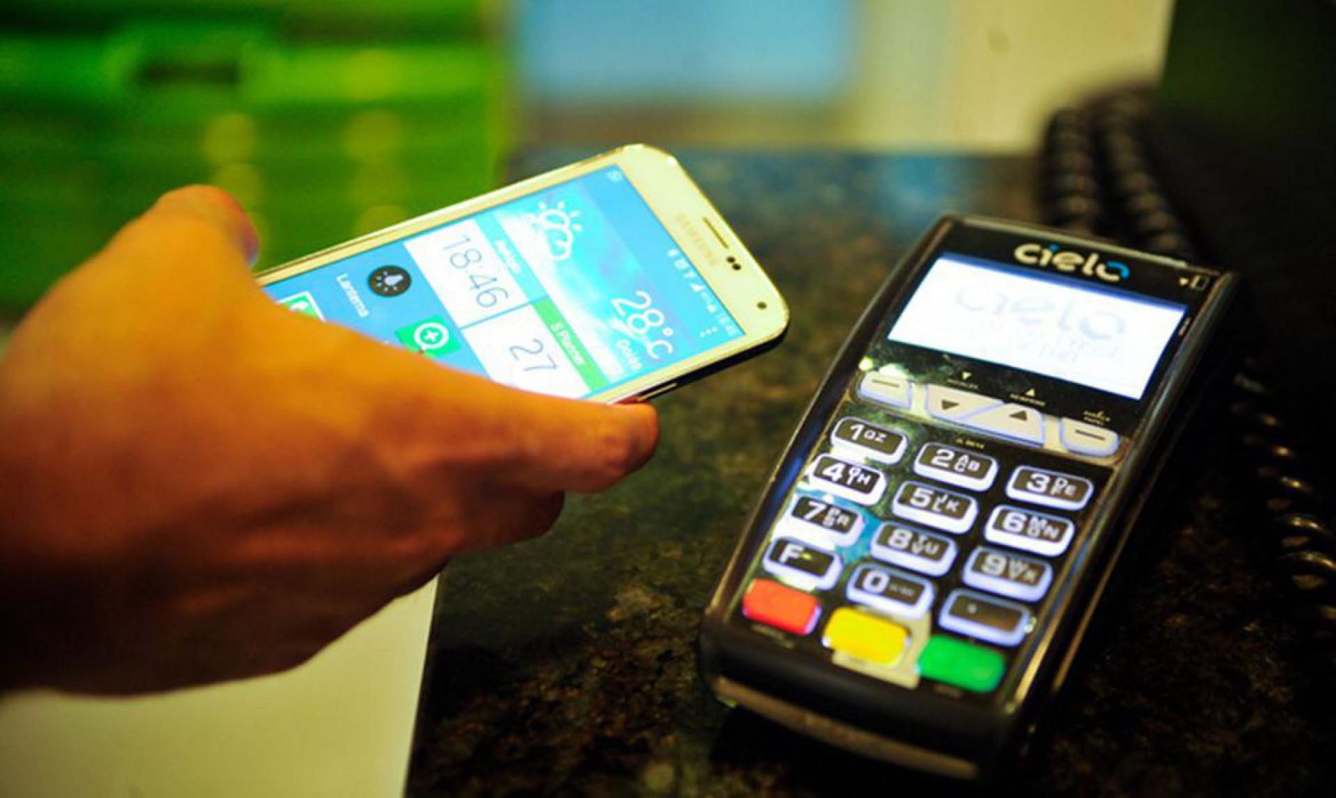 Foto mostra homem segurando celular próximo de máquina de cartão de crédito.