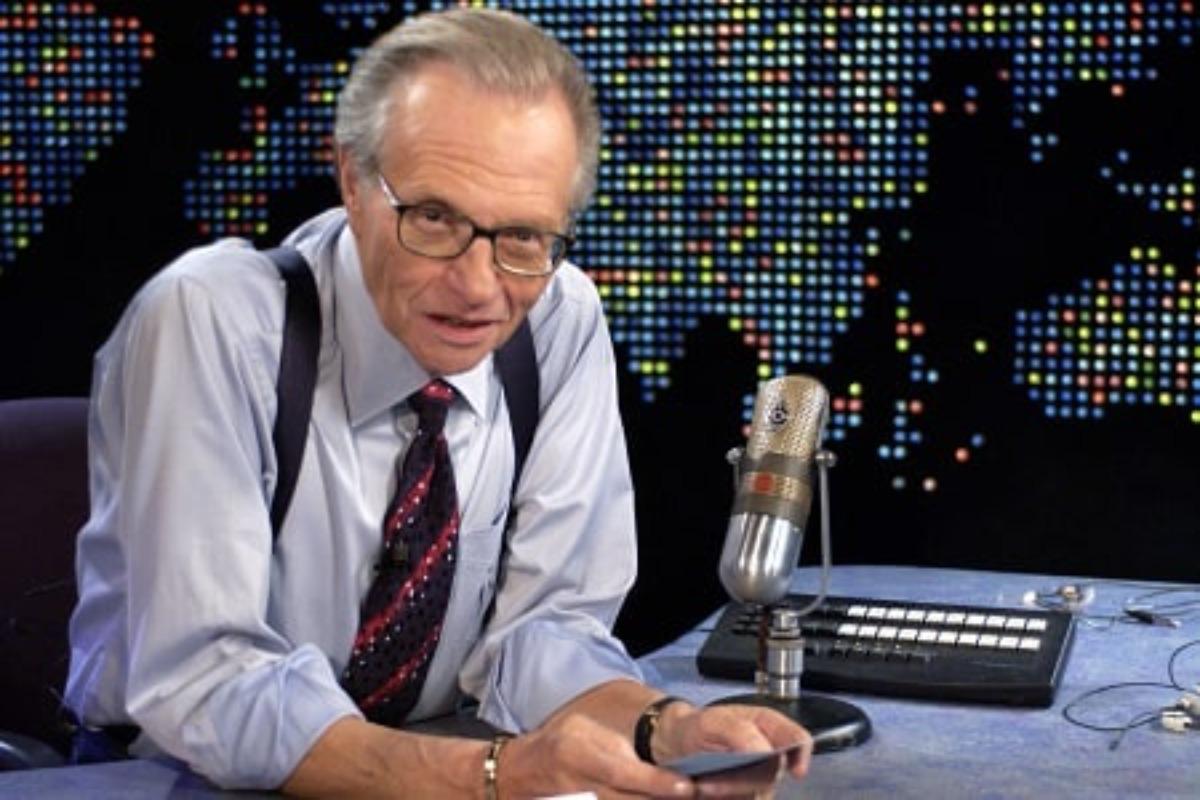 Imagem posada do jornalista Larry King sentado em uma bancada