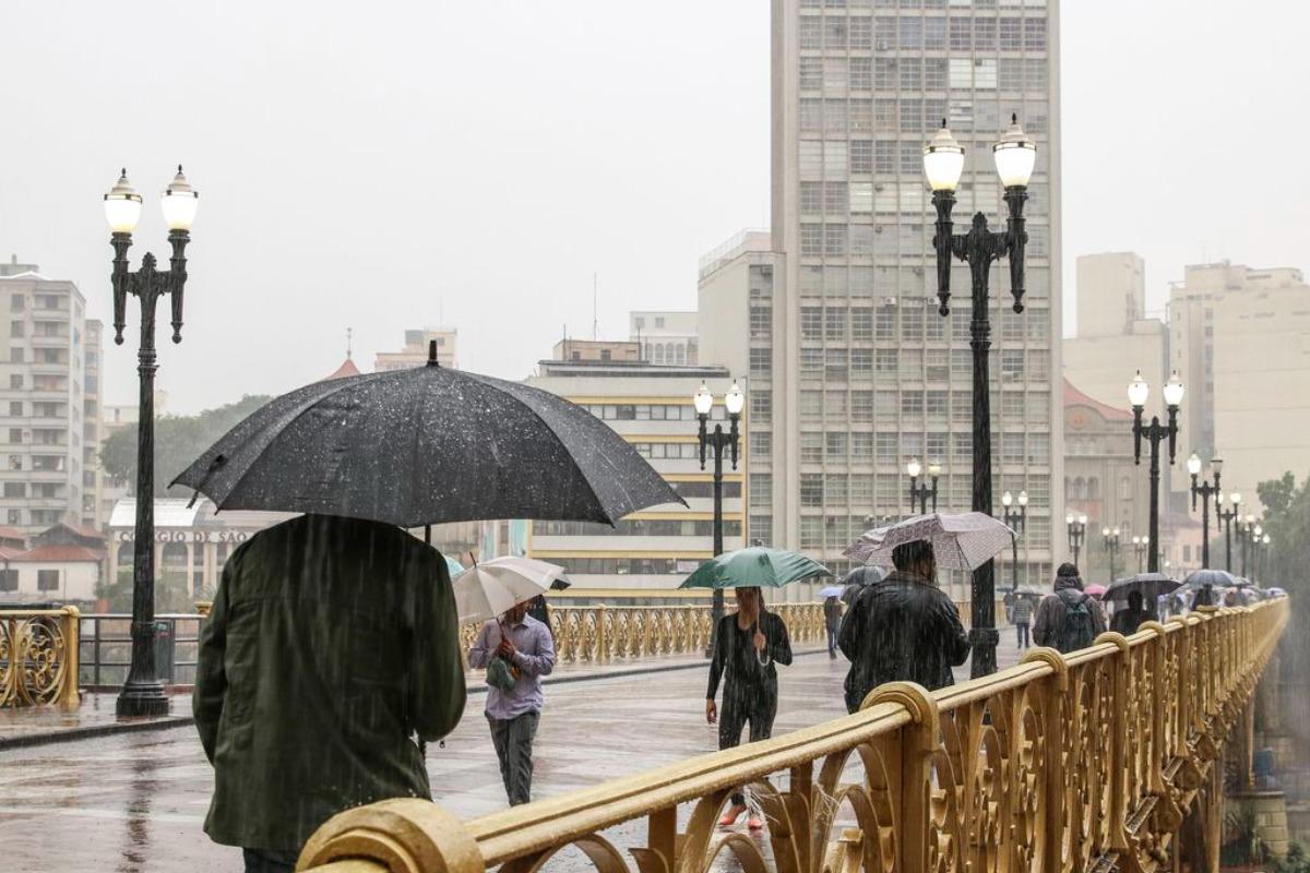 Imagem capturada no viaduto Santa Ifigênia,em São Paulo, mostra pessoas com guarda-chuva. Chuva em São Paulo. Previsão do tempo SP