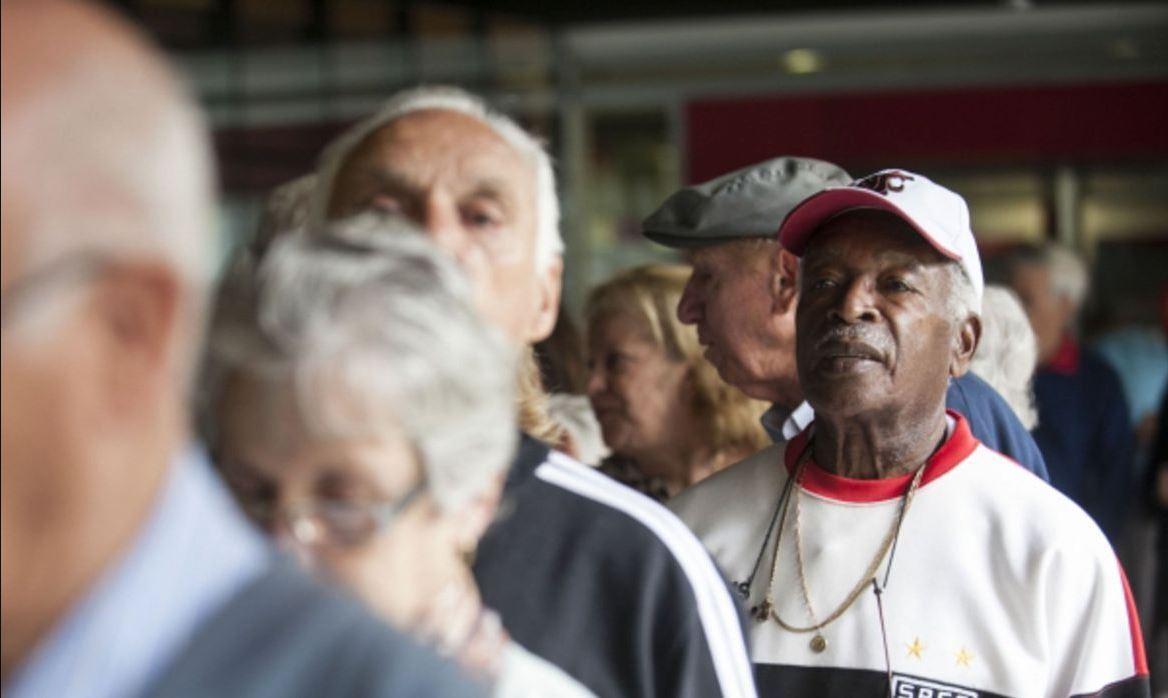 Foto mostra fila com pessoas idosas e aposentados.