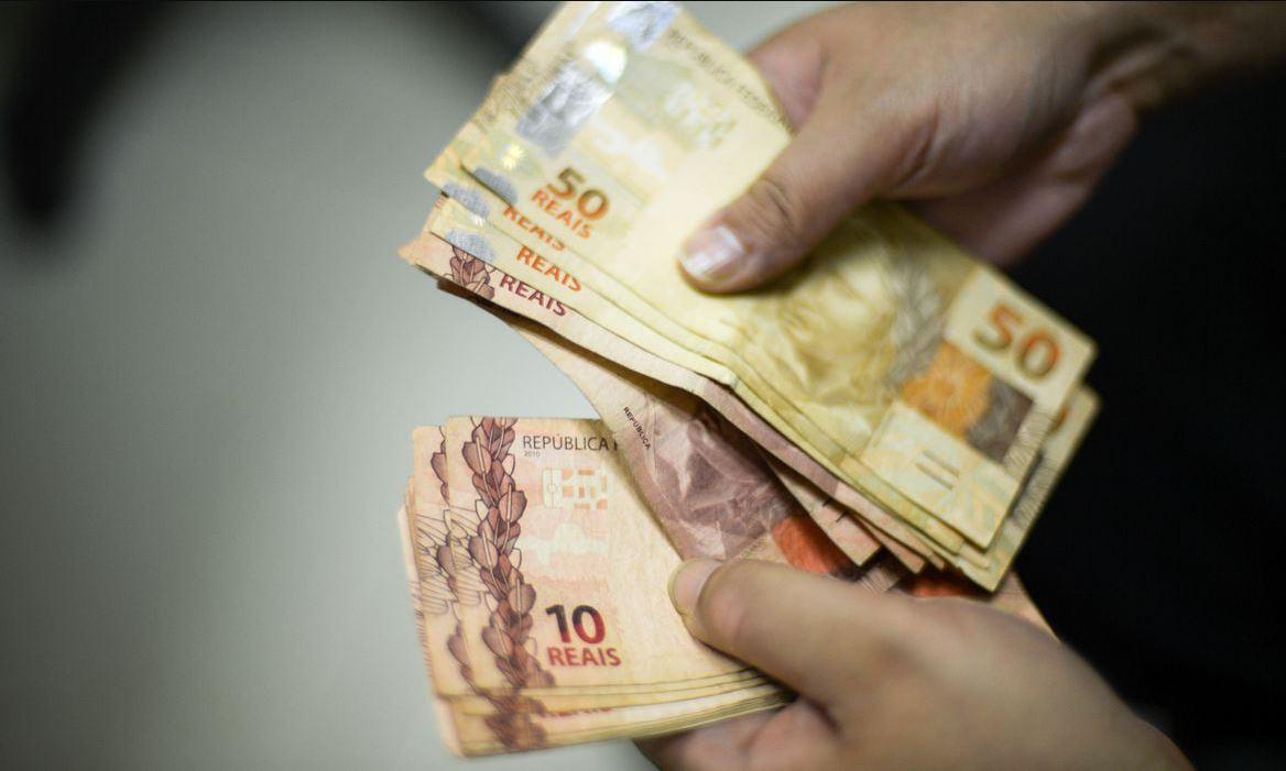 Foto com mãos de homem segurando e contando diversas notas de 50 reais e 10 reais
