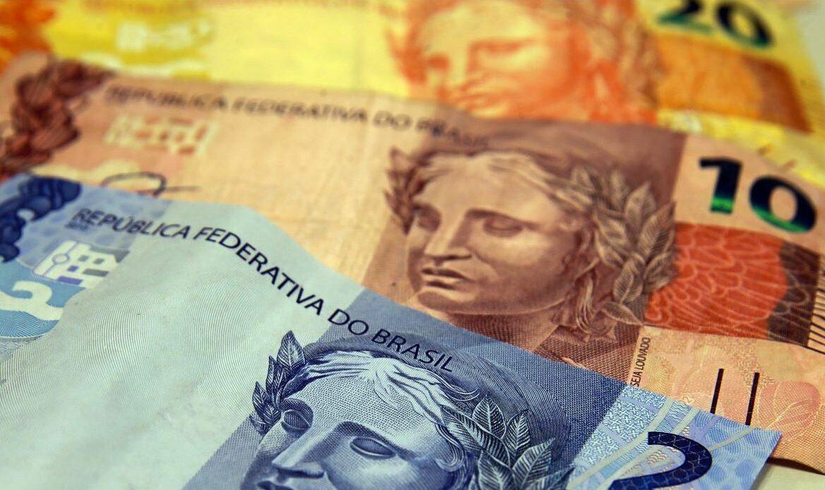 Foto mostra notas de 2, 10 e 20 reais, respectivamente.