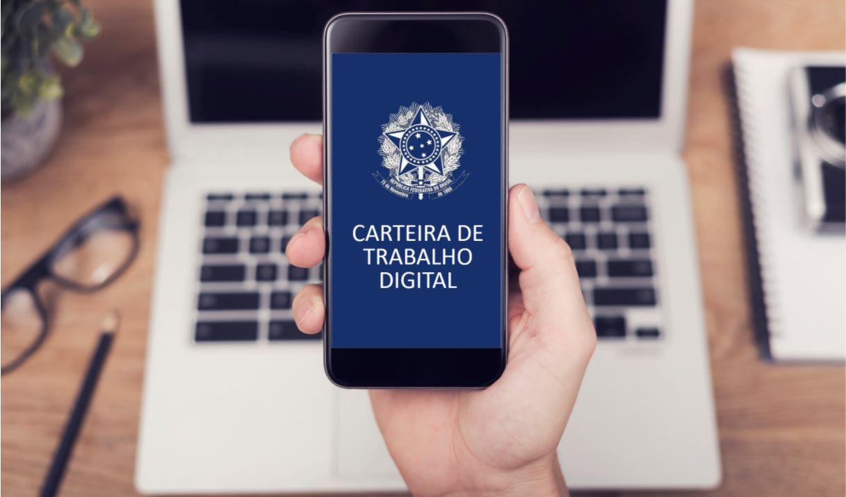 Foto mostra mãos segurando celular com aplicativo da carteira de trabalho digital aberta, e um notebook cinza aberto sobre a mesa de madeiraao fundo