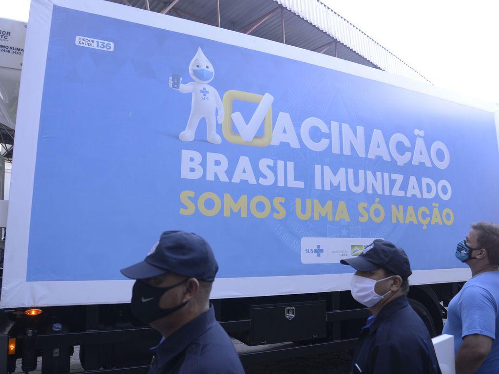 Imagem mostra agentes públicos com lotes das vacinas contra Covid-19