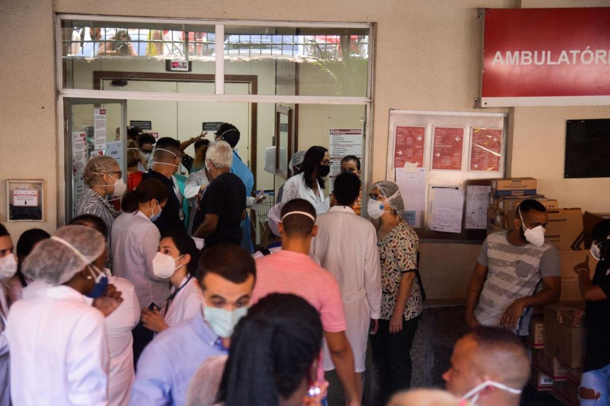 Imagem mostra pessoas na porta de um hospital. Pandemia afetou diretamente o PIB do país em 2020