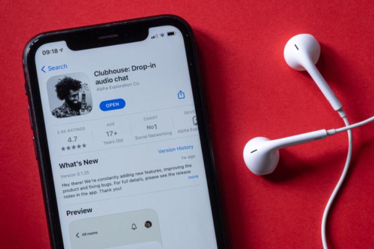 Imagem mostra celular e fone de ouvidos. Tela do aparelho exibe aplicativo Clubhouse