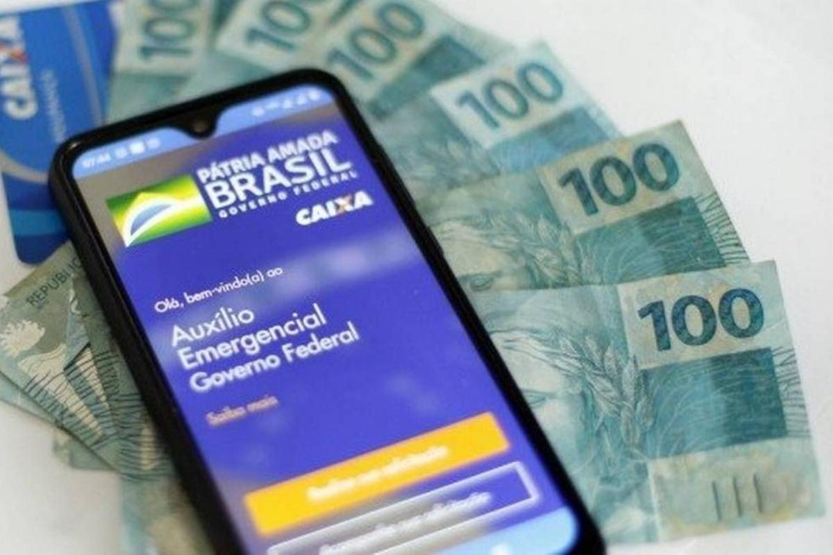 Imagem mostra celular com o aplicativo do Novo auxílio emergencial e notas de cem reais